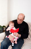 Grandpa reading red book to baby girl — Stock Photo