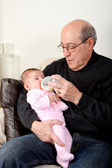 Grandpa bottle feeding baby girl — Stock Photo