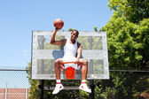 Champion basketball player sits in hoop — ストック写真