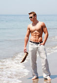 Handsome man standing on beach — Stock Photo