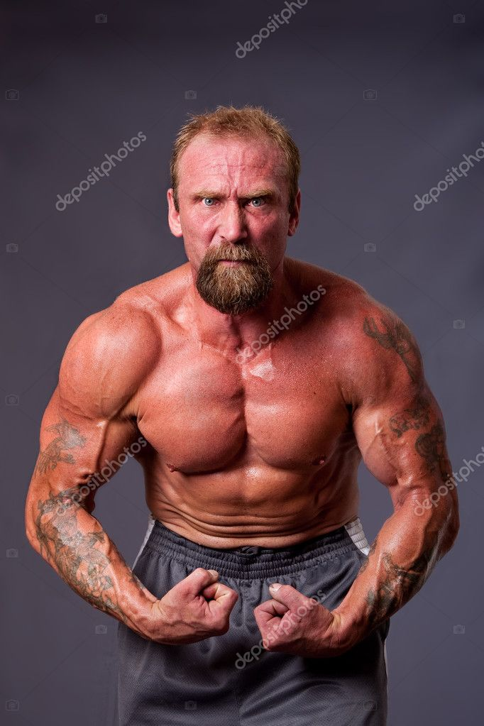 Middle aged Caucasian body builder man flexing muscles showing torso pecs, biceps and veins, isolated. — Stock Photo #2765297