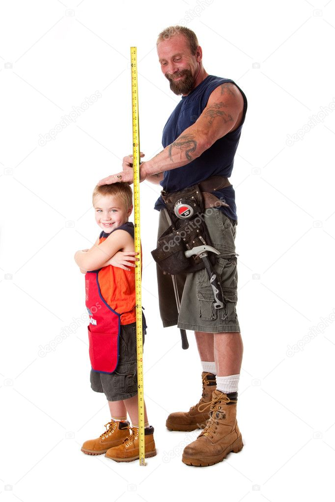 Father wearing tool belt with toy hammer and measuring tape, measures height of cute son dressed in orange apron, isolated. — Stock Photo #2765336