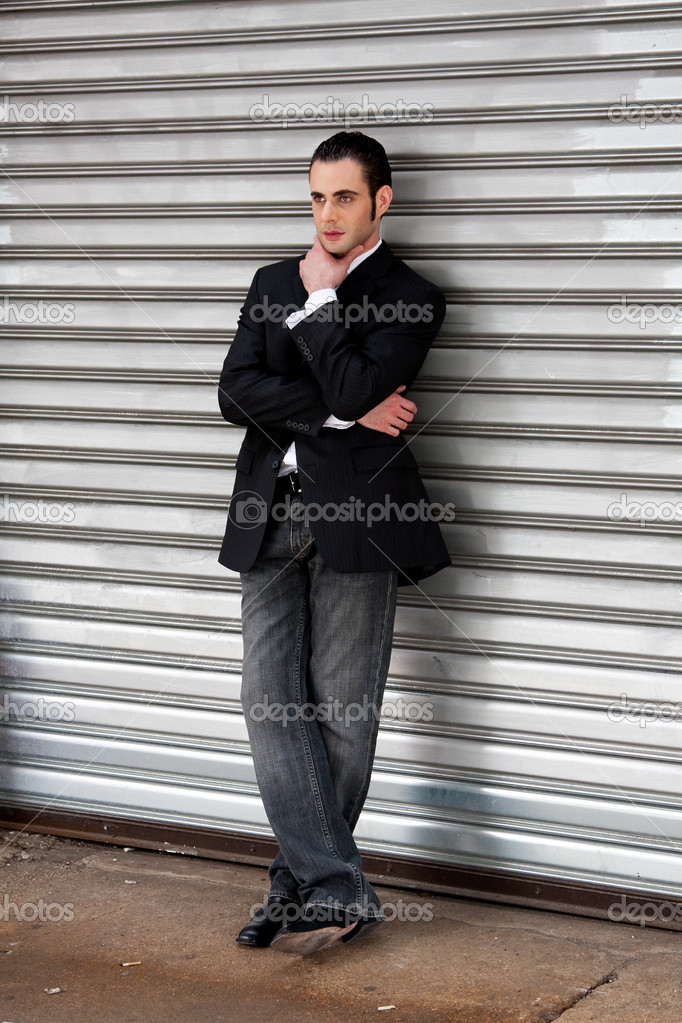 Handsome casual business man standing in front of and leaning against silver metal garage door with hand on chin thinking  Stock Photo #2765507