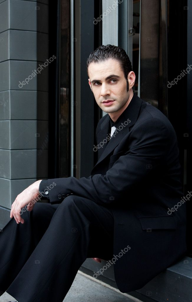 Handsome Caucasian business man in black suit sitting on street in front of a modern building — Stock Photo #2765528