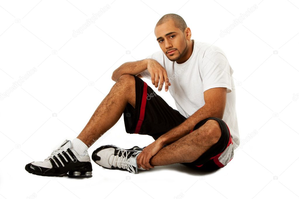Sporty handsome African Hispanic guy sitting on floor, isolated — Stock Photo #2766467
