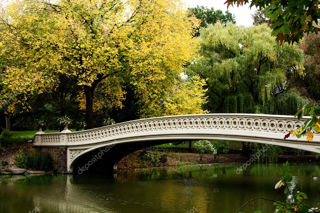Beautiful fall autumn scenery landscape of a white bridge over a peaceful body of water lake river.  Stock Photo #2768287