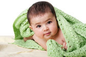 Cute happy baby between green blankets — Stock Photo