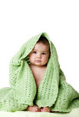 Cute baby sitting between green blanket. — Stock Photo