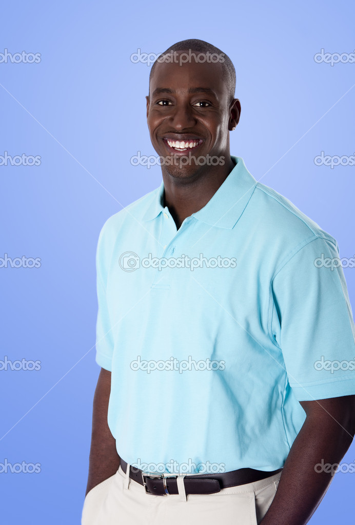 Handsome happy African American corporate business man smiling, wearing blue polo shirt, hands in pocket, standing, isolated. — Stock Photo #3220626