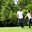 Happy couple running in park — Foto Stock