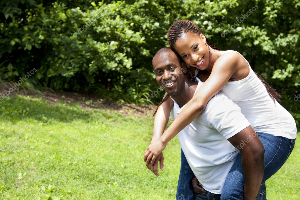 Beautiful happy smiling laughing young African American couple piggyback playing in the park, woman hugging man, wearing white shirts and blue jeans. — Stock Photo #3253265