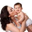 Mother kissing happy baby on cheek - Stock Photo