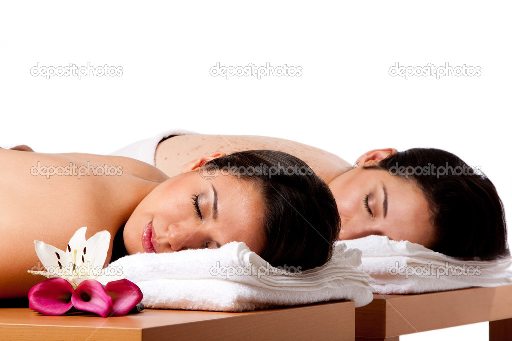 Two beautiful women friends laying on wooden tables with head on towels waiting for their massage in the spa, isolated. — Stock Photo #3435548