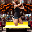 Fun girl jumping at Carousel - Stock Photo