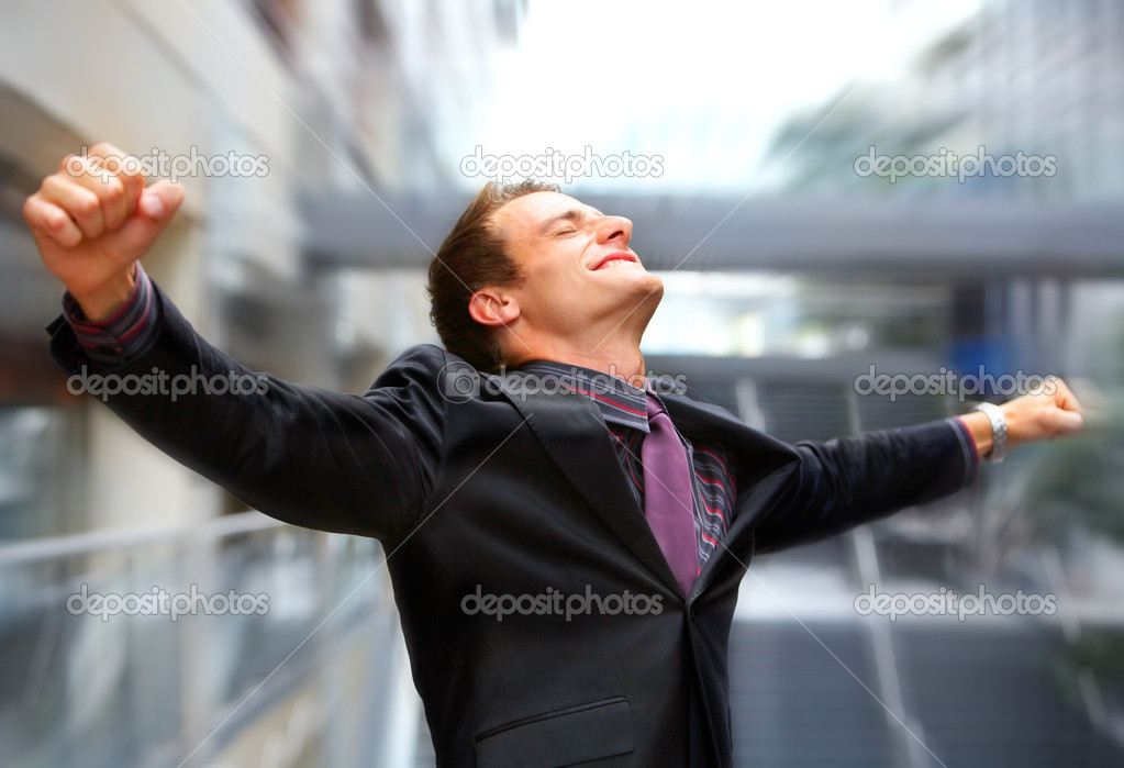 Champion business man standing with fists clenched in victory.  Stock Photo #3198118