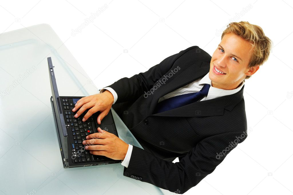 Business man working by desk - Portrait of a handsome young man in a business suit working.   Stock Photo #3198257