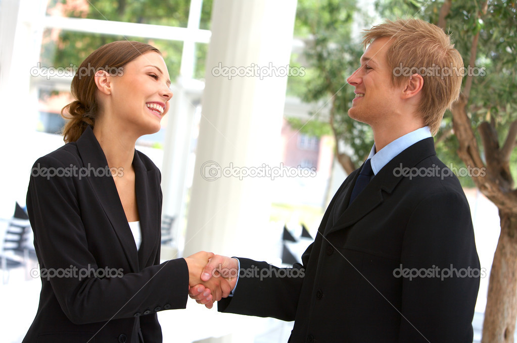 A businesswoman and businessman shaking hands.  — Stock Photo #3215587