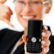 Business woman holding out phone - Stock Photo