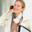 Beautiful business woman using her cell phone - Stock Photo