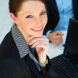 Young female in front of a workgroup - Stock Photo
