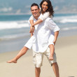 Young man giving piggyback to woman on beach - Photo