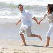 Young couple on beach, running hand in hand. - Stock Photo