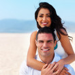 Smiling young couple on beach - Stockfoto