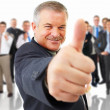 Older man giving the thumbs up in front - Stock Photo