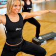 Women stepping in a fitness center - Stock Photo