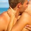 Royalty-Free Stock Photo: A Young Couple Kissing on the Beach