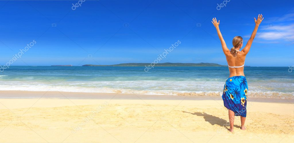 Picture fo a beautiful beach in the tropics, with a woman on the beach. Arms raised in well being.  Stock Photo #3220385