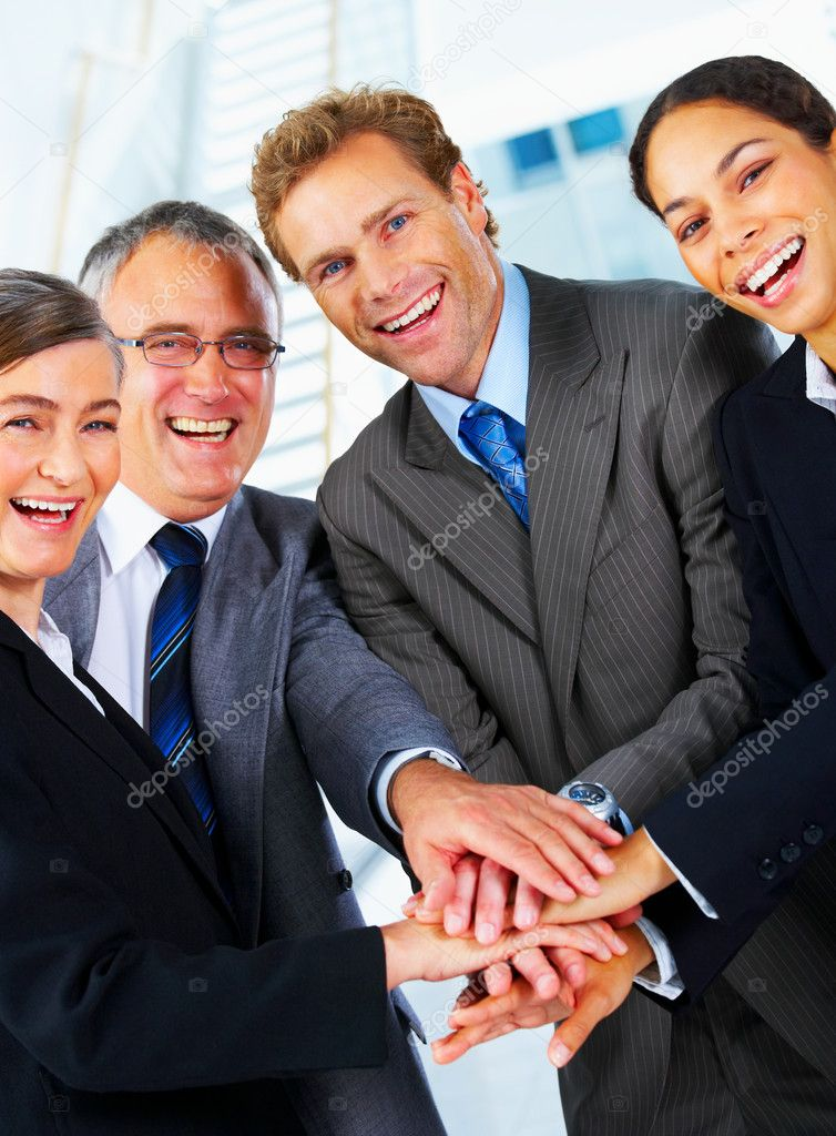 Handshake and teamwork. A group of business making a pile of hands in a light and modern office environment — Stockfoto #3220390