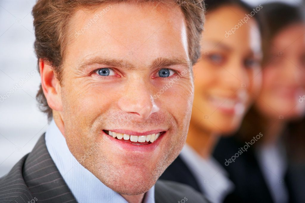 Business man attending a meeting with his colleagues in the background — Stock Photo #3220525