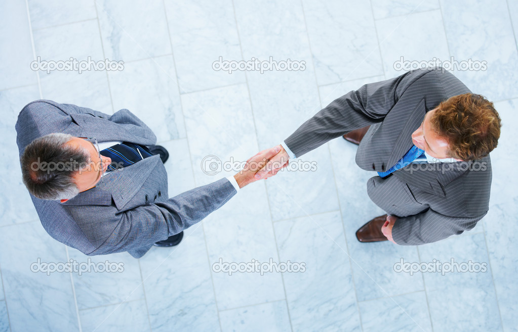 Business handshake and trust. Two businessmen shaking hands in a light and modern office environment. — Stock Photo #3220872
