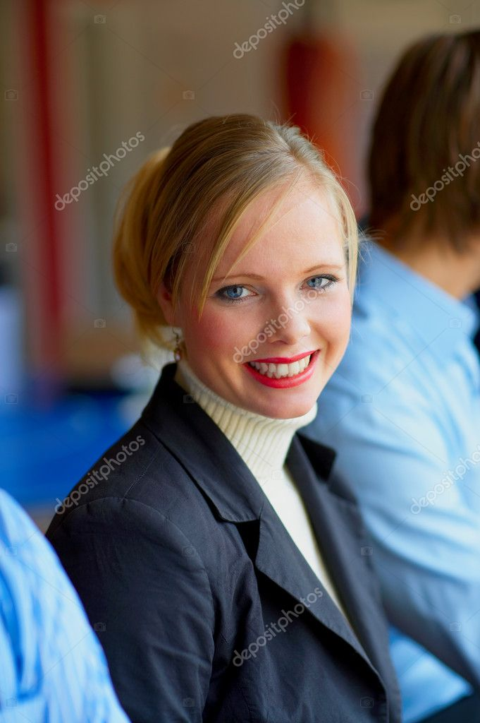 A portrait of a smiling young female in a cafe surrounded by her friends. This could be a workplace, college or business environment.  — Stock Photo #3220984