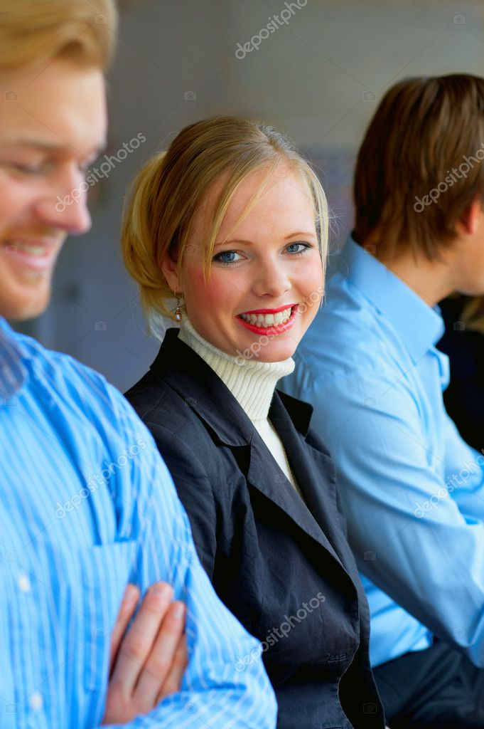 A portrait of a smiling young female in a cafe surrounded by her friends. This could be a workplace, college or business environment.  — Stock Photo #3220986