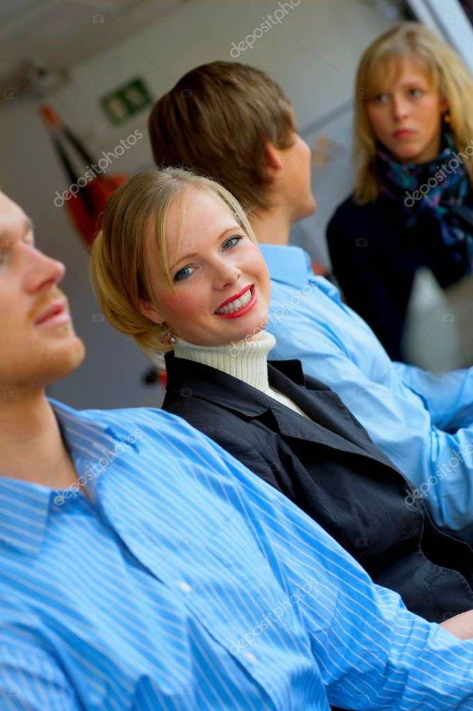 A portrait of a smiling young female in a cafe surrounded by her friends. This could be a workplace, college or business environment.  — Stock Photo #3220988