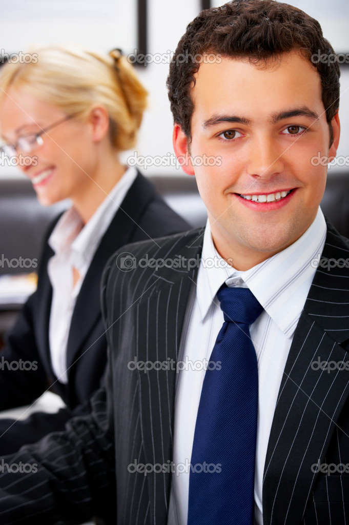 Portrait of a ambitious business man in an office environment. With a beautiful female colleague in the background. — Stock Photo #3221101