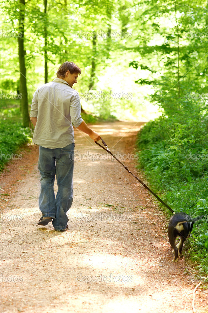 Man walking his best friend through the forest in the spring. — Stock Photo #3224983