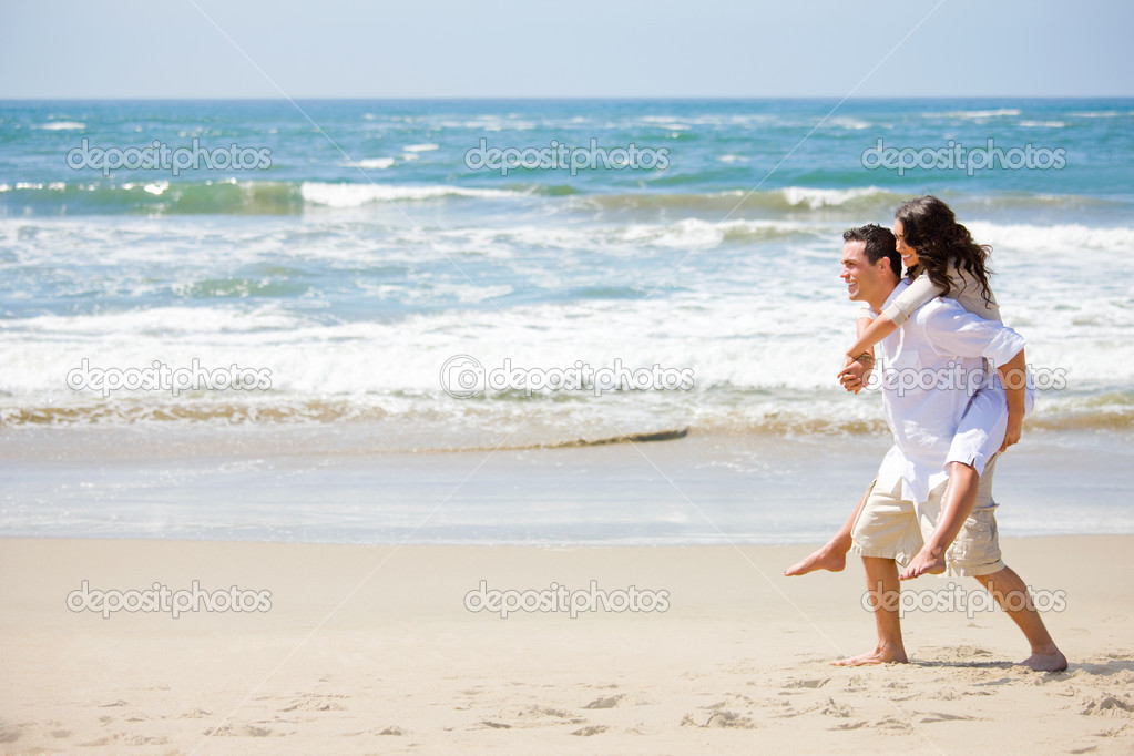 Full length of a young man giving piggyback to woman on beach. Couple in love on a sunny beach holiday. — Stock Photo #3225045