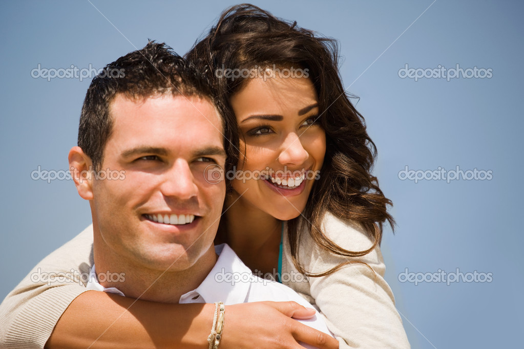 Smiling young man giving piggyback to woman on holiday. Girl hugging her boyfriend — Stock Photo #3225057