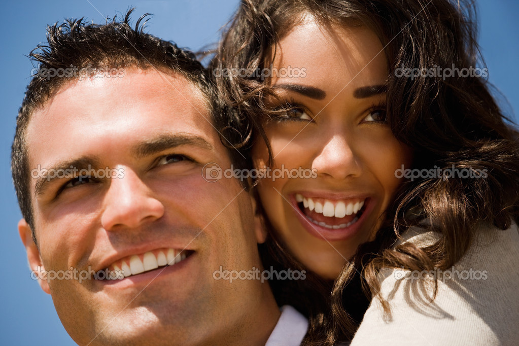 Close up of a smiling couple in love. Woman hugging the man, blue sky as background. — Stock Photo #3225063