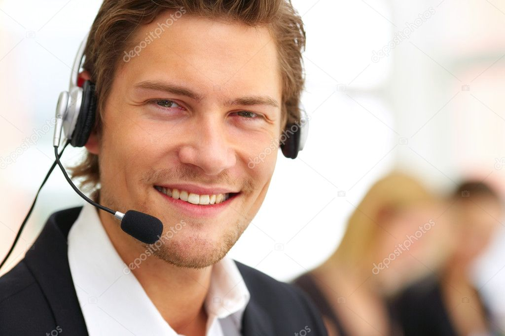 A friendly telephone operator in an office environment.  Stock Photo #3228587