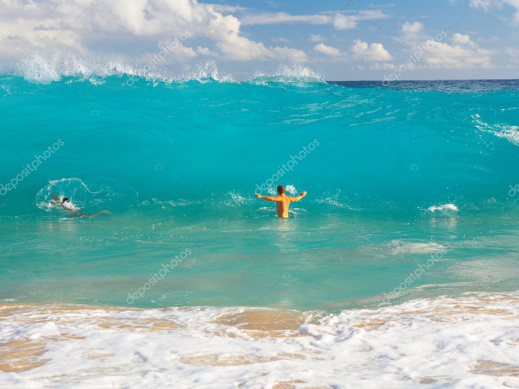 This is a shot of a man standing under a huge wave in Hawaii.  Stock Photo #3229245