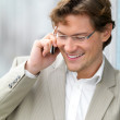 Royalty-Free Stock Photo: Young business man talking about work on his mobile phone