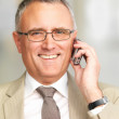 Royalty-Free Stock Photo: Senior business man talking on cell phone