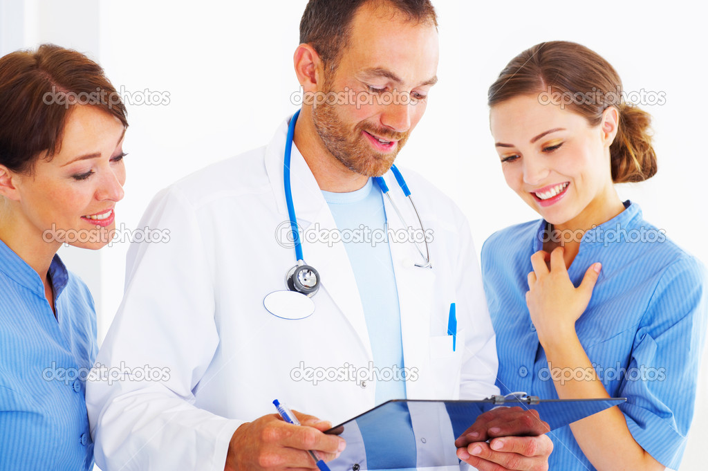 A doctor discussing a patients chart with two nurses — Stock Photo #3232065