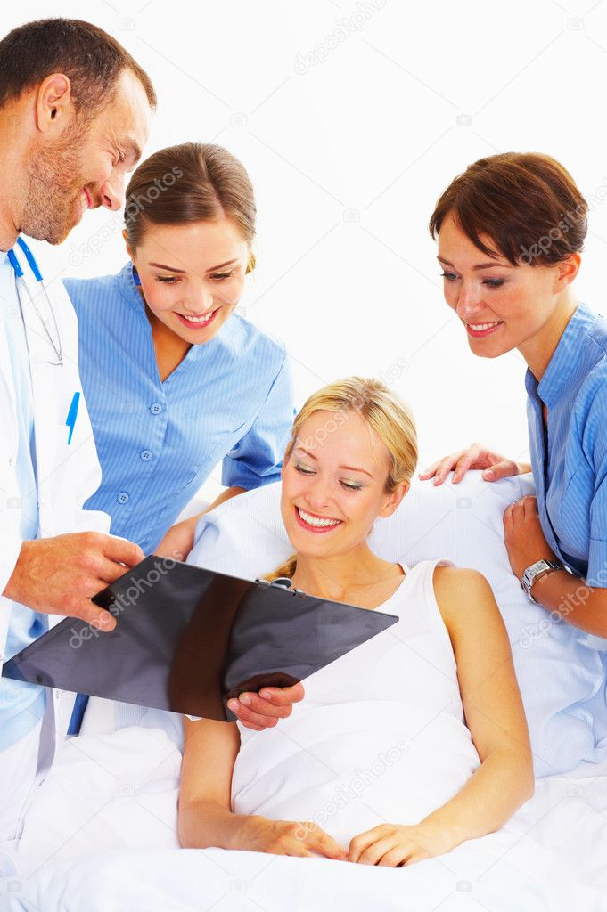 A doctor and two nurses discussing a patients charts with her. — Stock Photo #3232082