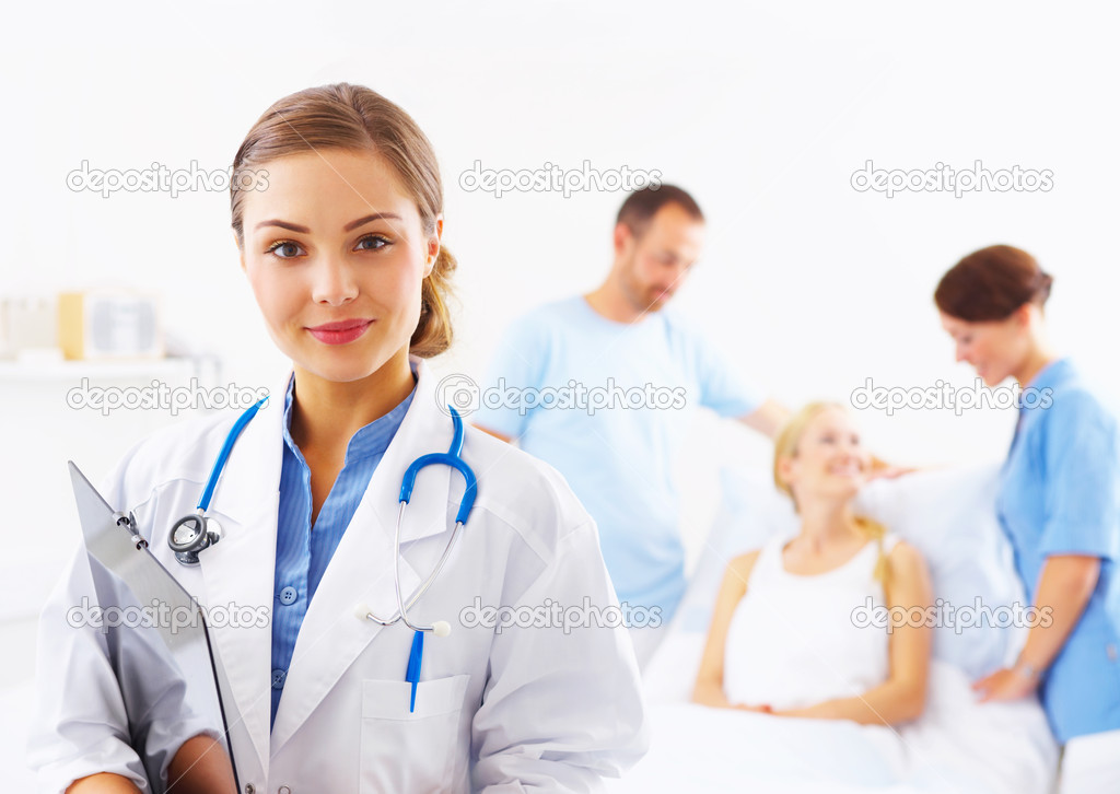 Portrait of a doctor with two of her co-workers talking with a patient in the background  Stock Photo #3232169