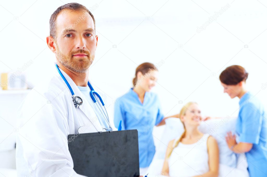 A portrait of doctor with two attractive nurses in the background — Stock Photo #3232175